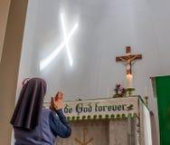 Freira católica que reza o rosário na frente do crucifixo com o feixe de luz que cria uma cruz na parede foto de stock royalty free