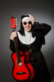A freira engraçada com jogo vermelho da guitarra Foto de Stock