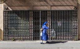 A freira no vestido azul apressa-se no calor do meio-dia ao longo do passeio Fotografia de Stock Royalty Free