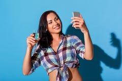 freistil Frau mit bloßer Bauchstellung lokalisiert auf blauer Wand mit dem Glas Champagner selfie auf Smartphone nehmend lizenzfreie stockfotos
