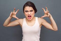 freistil Frauenstellung auf dem grauen Gesichtes Verziehen Gesichtes Verziehen und dem Gestikulieren furchtsam stockfotografie
