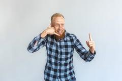 freistil Reife Mannstellung lokalisiert auf dem grauem darstellendem lächelndem aufgeregtem Zeigen der Anrufgeste herauf Lösung stockbilder