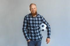 freistil Reife Mannstellung lokalisiert auf Grau mit dem Balllächeln entspannt lizenzfreies stockfoto