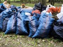 Freiwillig erbieten, N?chstenliebe, Reinigung, Leute und ?kologiekonzept - Abfalltaschen, die Bereich im Park s?ubern lizenzfreie stockfotos