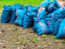 Freiwillig erbieten, N?chstenliebe, Reinigung, Leute und ?kologiekonzept - Abfalltaschen, die Bereich im Park s?ubern stockbild