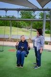 Freiwillig erbietend mit älteren Menschen, verbessert Frau ihre Sprachpraxis stockbild