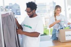 Freiwillige, die Kleidung aus einem Spendenkasten heraus nehmen Stockfotos