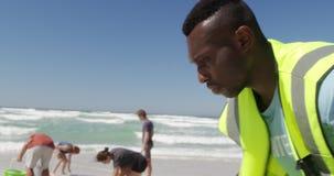 Freiwillige, die Strand an einem sonnigen Tag 4k säubern stock video footage