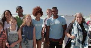 Freiwillige, die zusammen auf Strand im Sonnenschein 4k stehen stock video footage