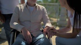 Freiwillige haltene Hand der angenehmen Frau eines wheelchaired Mannes im Ruhestand stock footage