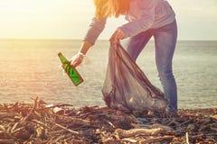 Freiwillige Hilfen der Frau den Strand des Abfalls säubern Tag der Erde und Verbesserung der Umwelts-Konzept Ökologie und Siche stockbild