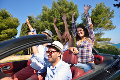 Freizeit-, Autoreise-, Reise- und Leutekonzept - glückliche Freunde, die in Cabrioletauto entlang Landstraße fahren stockfotos