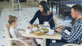 Freizeit der jungen Familie im Café Mitfühlende Mutter bittet um launisches wenig dauhter, um Gemüse zu essen Unterdessen ist Vat lizenzfreie stockfotografie