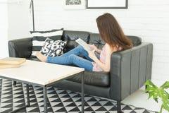 Freizeit, Technologie und Leutekonzept - junge Brunettefrau, die zu Hause Tablette verwendet stockbilder