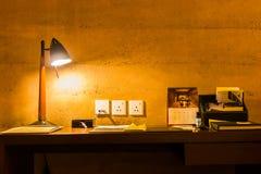 Freizeitarbeitsschreibtisch unter einer glühenden Lampe stockfotos