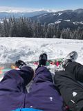 Freizeitferien in den Bergen auf dem Skibericht Beine des Paarjungen und des Mädchens vor dem schönen Schnee Lizenzfreies Stockbild