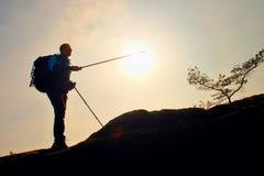 Fremdenführershow der richtige Weg mit Pfosten in der Hand Wanderer mit sportlichem Rucksackstand auf felsigem Standpunkt über ne Stockbilder