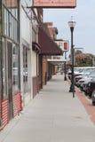 Fremont céntrico, Nebraska, acera con las tiendas y muestras y coches foto de archivo