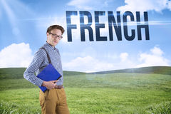 French against blue sky over green field. The word french and geeky student holding a notebook against blue sky over green field Stock Photo