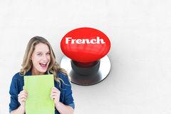 French against digitally generated red push button. The word french and smiling student holding notebook against digitally generated red push button Royalty Free Stock Images