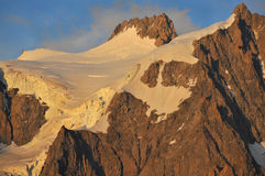 French Alps. Setting sun on the summit of the Aiguillet du Triolet in the mont blanc massif above Argentiere, in the french alps Stock Images