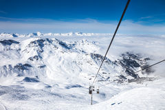 French Alps in Meribel. View from top of the mountain to clouds on the horizon and the funicular at French Alps in Meribel Stock Photos