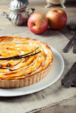 French apple tart with vanilla pod. French apple tart with apple compote and vanilla on a white plate royalty free stock image