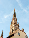 French architecture and cathedral spire against blue sky. Majestic spire of the Protestant St. Stephen`s Church French: Temple Saint-Etienne the main Reformed Stock Photo