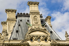 French Architecture: Lion Chimera and Women on Facade. Contrasting nicely against a cloudy blue sky, this tan and gray ornate building features a lion with green royalty free stock photos