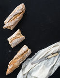 French baguette broken into pieces, white kitchen towel and vint Stock Image