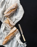 French baguette broken into pieces on a white kitchen towel with Stock Photo