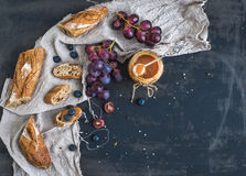 French baguette cut into pieces, red grapes, blueberry and salt caramel sauce on rustic dark background Royalty Free Stock Images