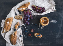 French baguette cut into pieces, red grapes Royalty Free Stock Photos