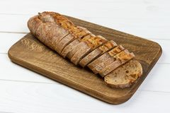 French Baguette on cutting board on white rustic table Royalty Free Stock Photo