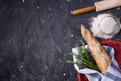 French Baguette with rosemary wrapped in a towel in red basket and whole grain flour, rolling pin on rustic background. Top view, Stock Photos