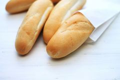 French baguettes, loaves on a light wooden background. Bakery and fresh bread concept stock image