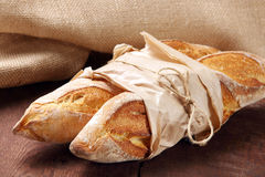 French baguettes in paper on wooden background Stock Image