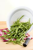 French beans, raw. Washed fresh french beans tumbling from colander with knife and checkered napkin stock images