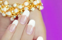 French beautiful manicures. French beautiful manicures decoration on a purple background stock photo