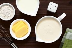 French Bechamel or White Sauce. Homemade French Bechamel or White Sauce served in sauce boat with ingredients on the e flour, butter, milk, photographed overhead stock photo