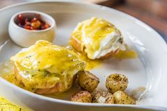 French Benedict breakfast. Two poached eggs on English muffin, doused generously with homemade hollandaise and served with soupy corn and parsley potatoes Royalty Free Stock Images