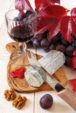 French blue cheese, red grapes, scarlet leaves and wineglass Royalty Free Stock Photography