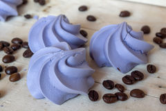 French blue meringue cookies and coffee beans. On white wooden background Royalty Free Stock Image