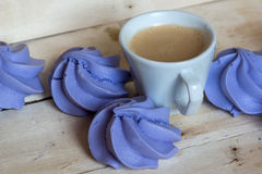 French blue meringue cookies and cup of coffee. On white wooden background Royalty Free Stock Image