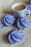 French blue meringue cookies and cup of coffee. On white wooden background Stock Image