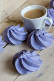 French blue meringue cookies and cup of coffee on  wooden background. French blue meringue cookies and cup of coffee on white wooden background Royalty Free Stock Photography