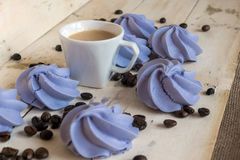 French blue meringue cookies and cup of coffee on  wooden background. French blue meringue cookies and cup of coffee on white wooden background Stock Photography