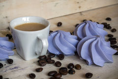 French blue meringue cookies and cup of coffee on wooden background. French blue meringue cookies and cup of coffee on white wooden background Stock Photos