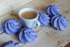 French blue meringue cookies and cup of coffee on wooden background. French blue meringue cookies and cup of coffee on white wooden background Royalty Free Stock Image