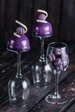 French blueberry mousse cake served on inverted wine glasses and macaroons in one of these on wood background Royalty Free Stock Images